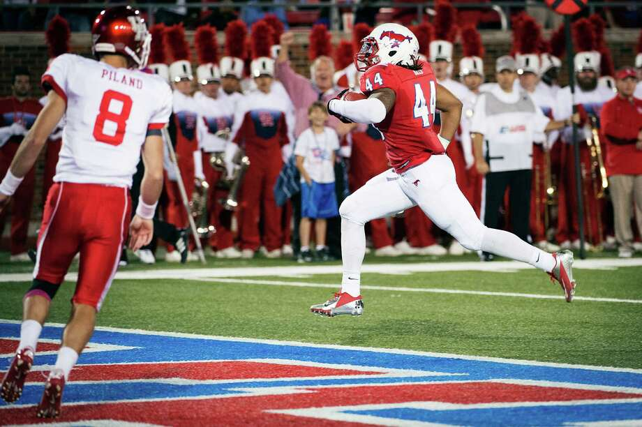 SMU linebacker Taylor Reed, right, scores a touchdown after intercepting a pass by Houston quarterback David Piland, one of nine UH turnovers Thursday. Photo: Smiley N. Pool / Houston Chronicle