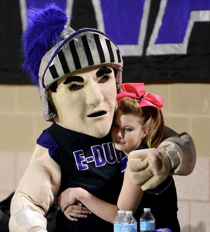 A Warren cheerleader gets a hug from the Warren Mascot during a district Football game between the Warren Warriors and the o'Connor Panthers at Farris Stadium in San Antonio, Saturday, October 19, 2012.