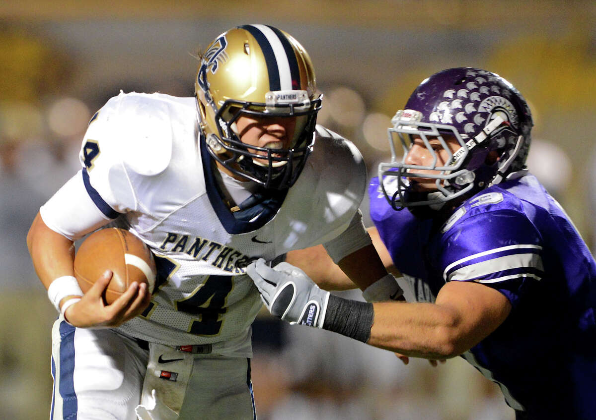 O'Connor quarterback Zach Galindo (14) tries to escape the grasp of Warren's Jerry Robertson (33) during a district football game between the Warren Warriors and the o'Connor Panthers at Farris Stadium in San Antonio, Saturday, October 19, 2012. John Albright / Special to the Express-News.