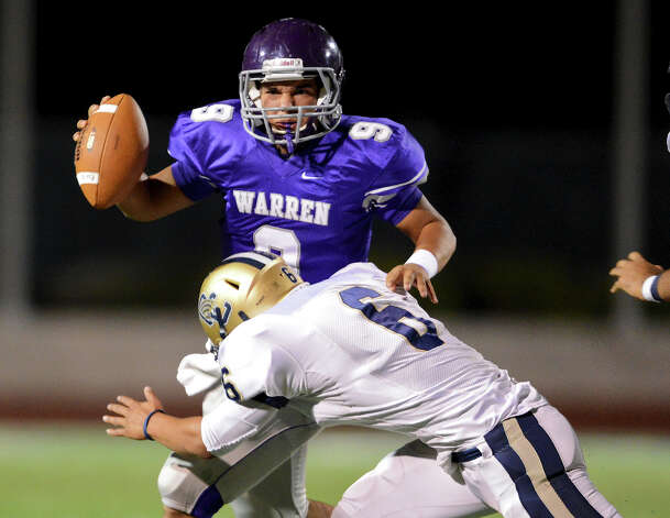 Warren quarterback Ryan Larson (9) is tackled by O'Connor's Steven Cantu (6) during a district football game between the Warren Warriors and the o'Connor Panthers at Farris Stadium in San Antonio, Saturday, October 19, 2012.