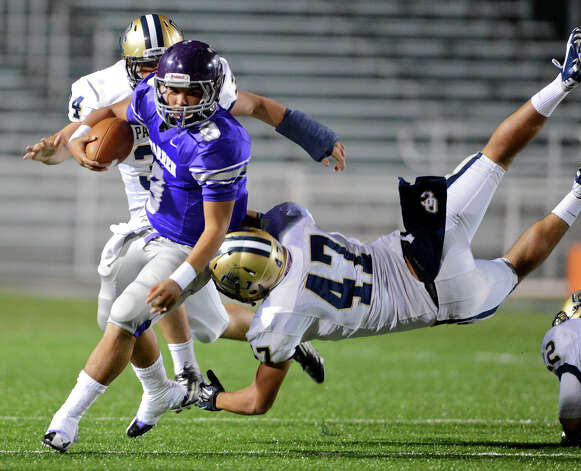 Warren quarterback Ryan Larson (9) tries to escape the grasp of O'Connor's Daniel Statzenburger (47) during a district football game between the Warren Warriors and the o'Connor Panthers at Farris Stadium in San Antonio, Saturday, October 19, 2012.