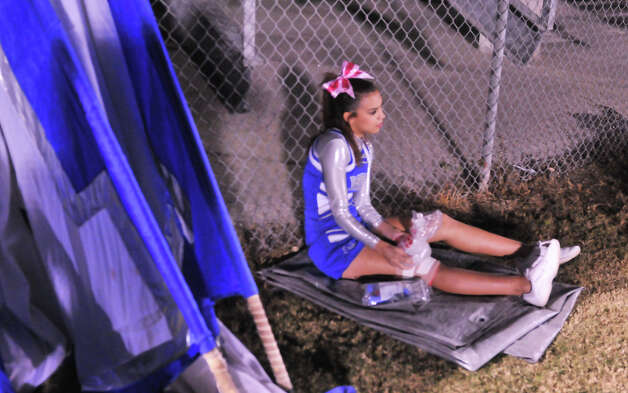 Lanier High School cheerleader Eric Gomez ices a sore knee at halftime of their game versus Brennan Friday evening. Photo: Robin Jerstad, Express-News