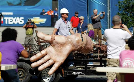 A worker hangs onto the hand of Big Tex as he his carted away after he burned at the State Fair of Texas Friday, Oct. 19, 2012, in Dallas. The iconic structure was destroyed Friday when flames engulfed his 52-foot-tall frame. Photo: LM Otero, Associated Press / AP