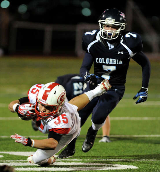 Guilderland's Marcus Knodler (35), center, gets tripped up as Columbia's Matt Briggs (7), right, def