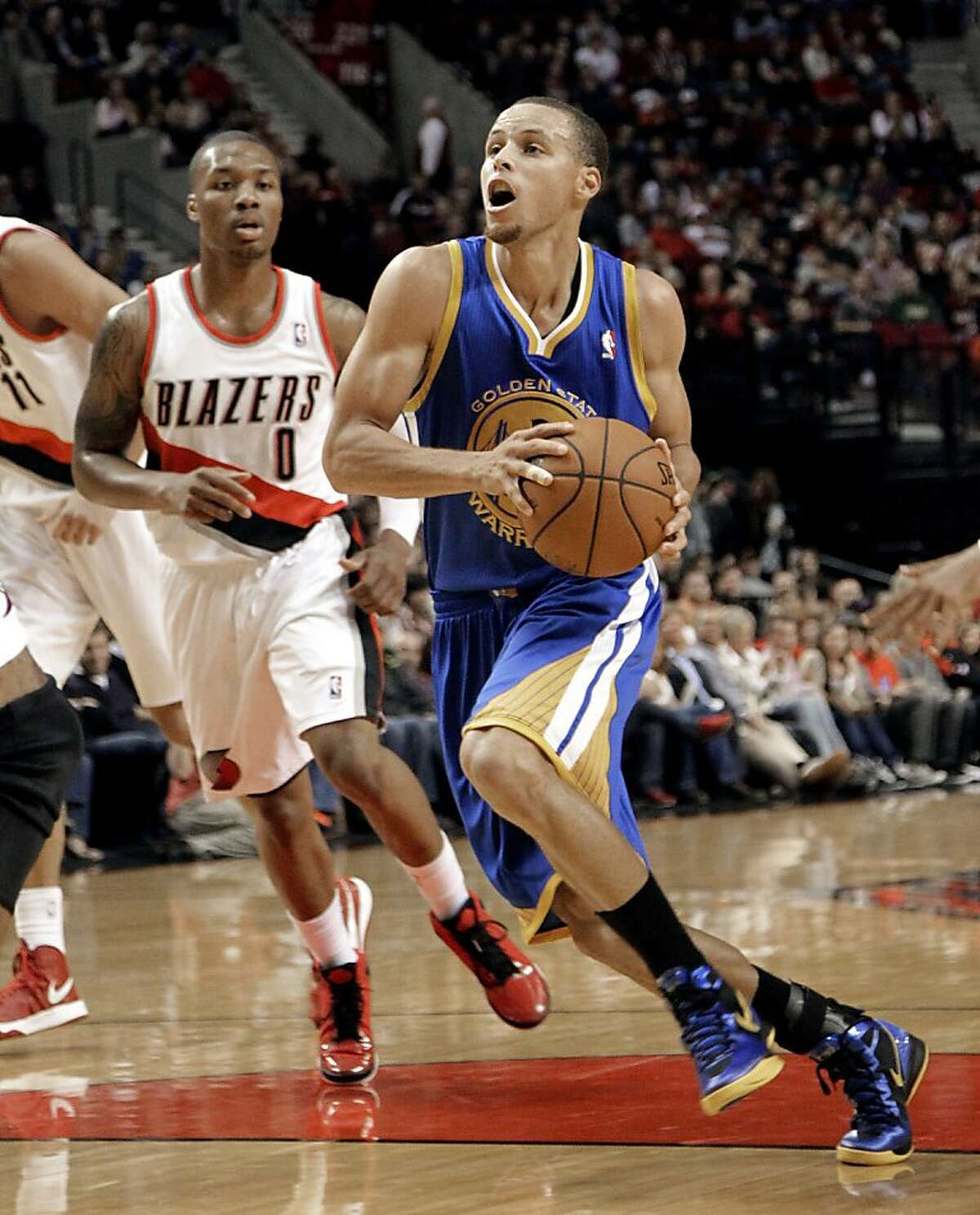 Golden State Warriors guard Stephen Curry, right, drives to the basket past Portland Trail Blazers guard Damian Lillard during the first quarter of an NBA preseason basketball game in Portland, Ore., Friday, Oct. 19, 2012. (AP Photo/Don Ryan)