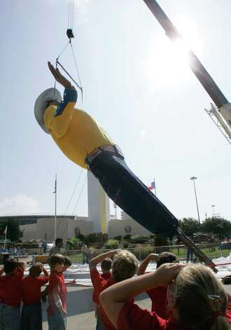 Children watch as Big Tex is put into place in preparation for the Sate Fair of Texas in Dallas, Monday, Sept. 22, 2008. Big Tex is wearing new jeans and a new yellow cowboy-style yellow shirt. This is the first time Big Texas has ever worn yellow. Photo: Donna McWilliam, Associated Press / AP2008
