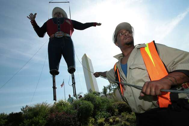 Sedric Horton holds a guide line as Big Tex is set in place for the 60th time for the Texas State Fair at Fair Park in Dallas Sept. 24, 2012. Photo: Nathan Hunsinger, Dallas Morning News / 10015425A