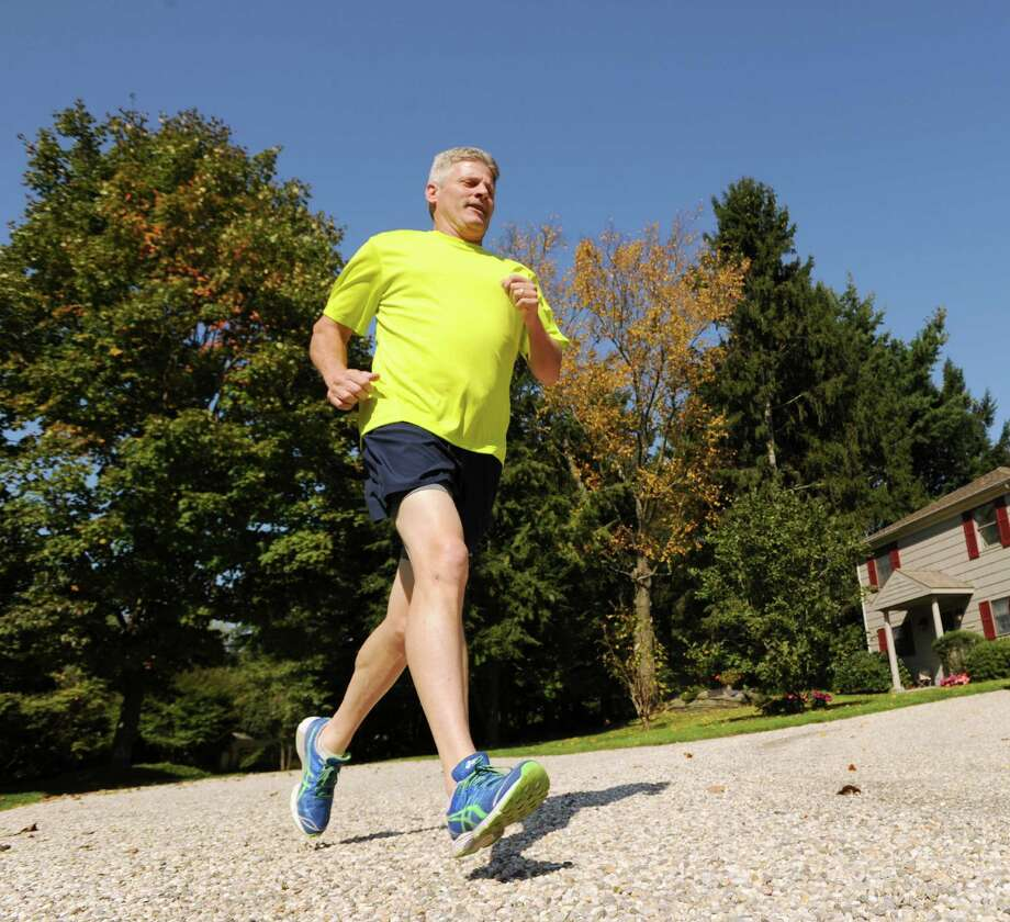 John McCarthy runs on the driveway of his Round Hill Road in Greenwich, Friday afternoon, Oct. 5, 2012. McCarthy will be running in the ING New York City Marathon Nov. 4 to raise money for the Hole in the Wall Gang Camp, a camp for kids with cancer and serious blood diseases that his son, Jeremiah, a cancer survivor, attended. Photo: Bob Luckey / Greenwich Time