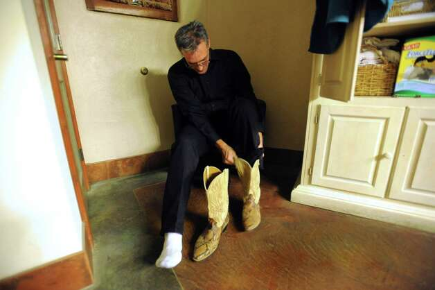 Charlie Hewitt dons his cowboy boots in a dressing room at the One World Theater. He was preparing to perform with singer Michael Grimm. The performance would be a dream come true for Hewitt, who suffers from liver cancer. Photo: Billy Calzada, San Antonio Express-News / © 2012 San Antonio Express-News