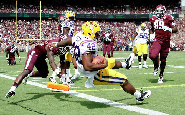 LSU running back Michael Ford (42) gets past the Texas A&M defense for the Tigers first touch down during the second quarter of a NCAA football game, Saturday, Oct. 20, 2012, in College Station. Photo: Nick De La Torre, Houston Chronicle / © 2012  Houston Chronicle