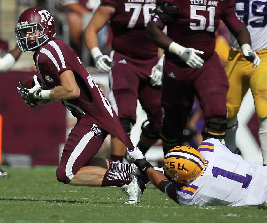 Texas A&M receiver Ryaqn Swope (25) is brought down by LSU safety Eric Reid during the first quarter of a NCAA football game, Saturday, Oct. 20, 2012, in College Station. Photo: Nick De La Torre, Houston Chronicle / © 2012  Houston Chronicle