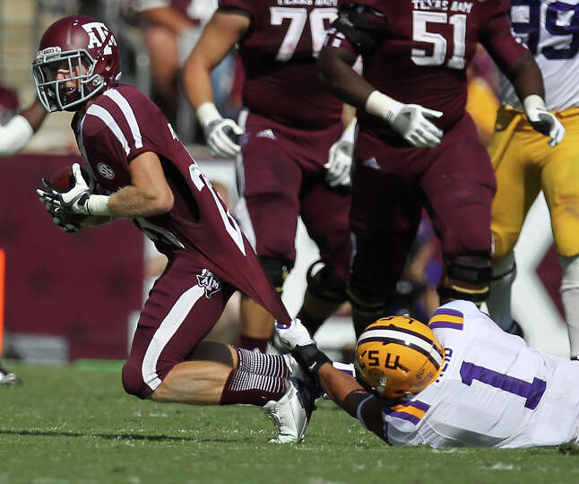 Texas A&M receiver Ryaqn Swope (25) is brought down by LSU safety Eric Reid during the first quarter