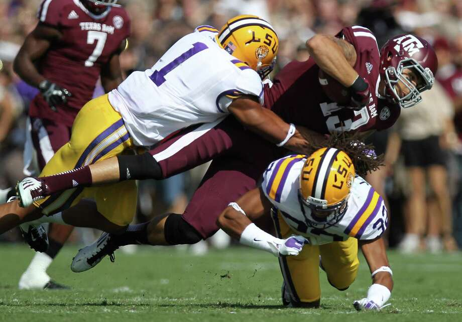Texas A&M receiver Mike Evans (13) is brought down by LSU's Eric Reid (1) and Jalen Collins during the first quarter of a NCAA football game, Saturday, Oct. 20, 2012, in College Station. Photo: Nick De La Torre, Houston Chronicle / © 2012  Houston Chronicle