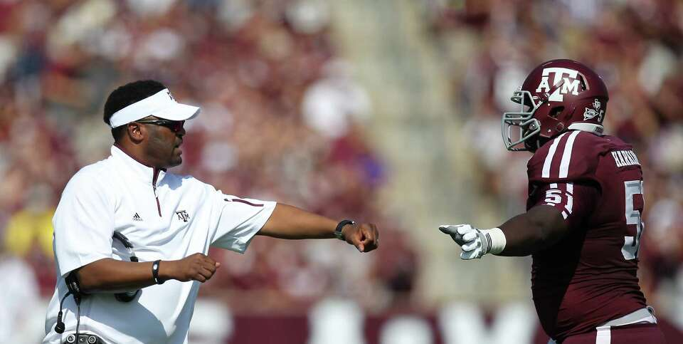 Texas A&M head coach Kevin Sumlin gives offensive lineman Jarvis Harrison a high five after the Aggi