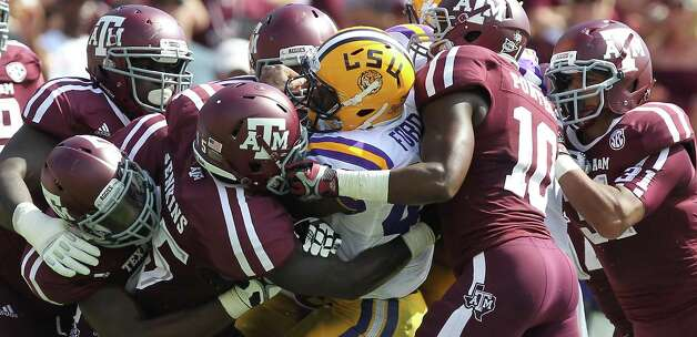 LSU running back Michael Ford is wrapped up by a host of Texas A&M defenders during the second quarter of a NCAA football game, Saturday, Oct. 20, 2012, in College Station. Photo: Nick De La Torre, Houston Chronicle / © 2012  Houston Chronicle