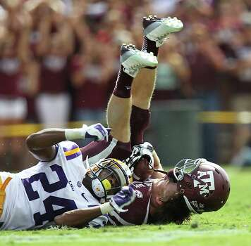 A&M's Ryan Swope (25) gets his helmet knocked off as he came up the a first down against LSU's Tharold Simon (24) during the first half of a college football game at Kyle Stadium, Saturday, Oct. 20, 2012, in College Station. Photo: Karen Warren, Houston Chronicle / © 2012  Houston Chronicle