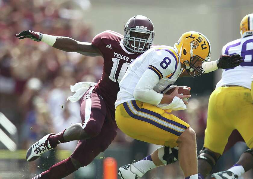 LSU's QB Zach Mettenberger (8) is sacked by A&M's Sean Porter (10) during the first half of a colleg