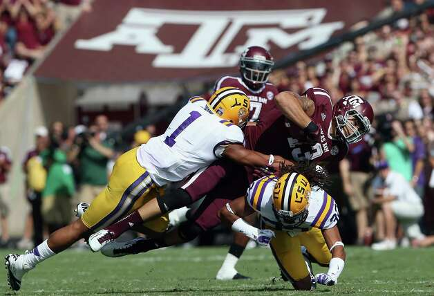 Mike Evans (13) of the Texas A&M Aggies runs the ball against Eric Reid (1) and Jalen Collins (32) of the LSU Tigers at Kyle Field on October 20, 2012 in College Station, Texas. Photo: Ronald Martinez, Getty Images / 2012 Getty Images