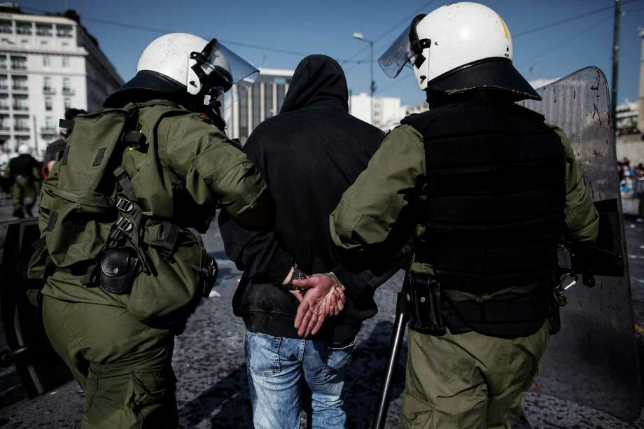 Riot police detain a demonstrator during clashes amidst a protest march in Athens, Greece, Oct. 18, 2012. Tens of thousands of Greeks joined a second nationwide strike in three weeks Thursday, moving to bring the country to a near-standstill in a bid to show European Union leaders that fresh austerity cuts would be crippling. Photo: ANGELOS TZORTZINIS, New York Times / NYTNS