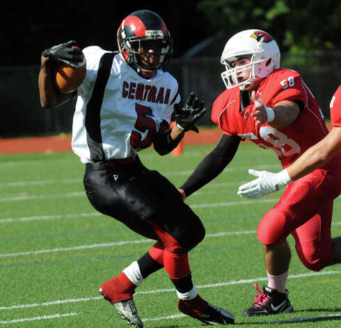 Central's Mykel Morris looks for yardage as Greenwich's Alex McGee closes in as Greenwich High School hosts Bridgeport Central in a football game in Greeniwch, Conn., Oct. 20, 2012. Photo: Keelin Daly / Stamford Advocate Freelance