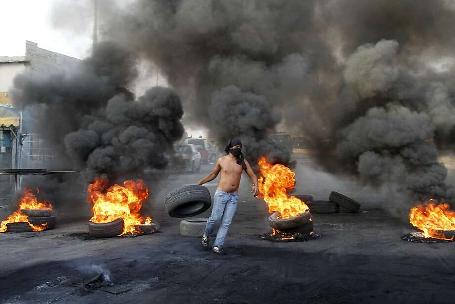 A man carries a tire to add to burning piles used as a roadblock in the southern port city of Sidon, Lebanon, during a protest of the killing of the country's intelligence chief and seven other people. Photo: Mohammed Zaatari, Associated Press