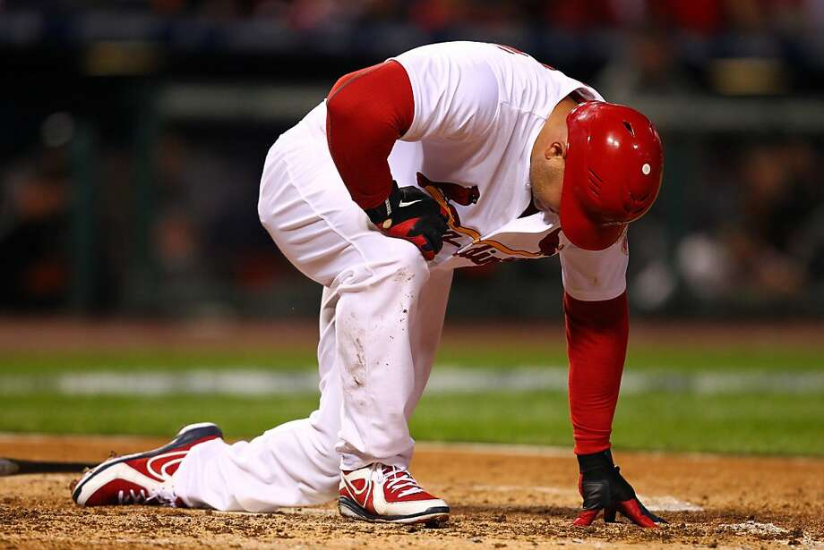 Matt Holliday, here brought down by a foul ball in the eighth inning of the Cardinals' NLCS Game 3 victory, struck out three times Friday as the Giants stayed alive. Photo: Dilip Vishwanat, Getty Images