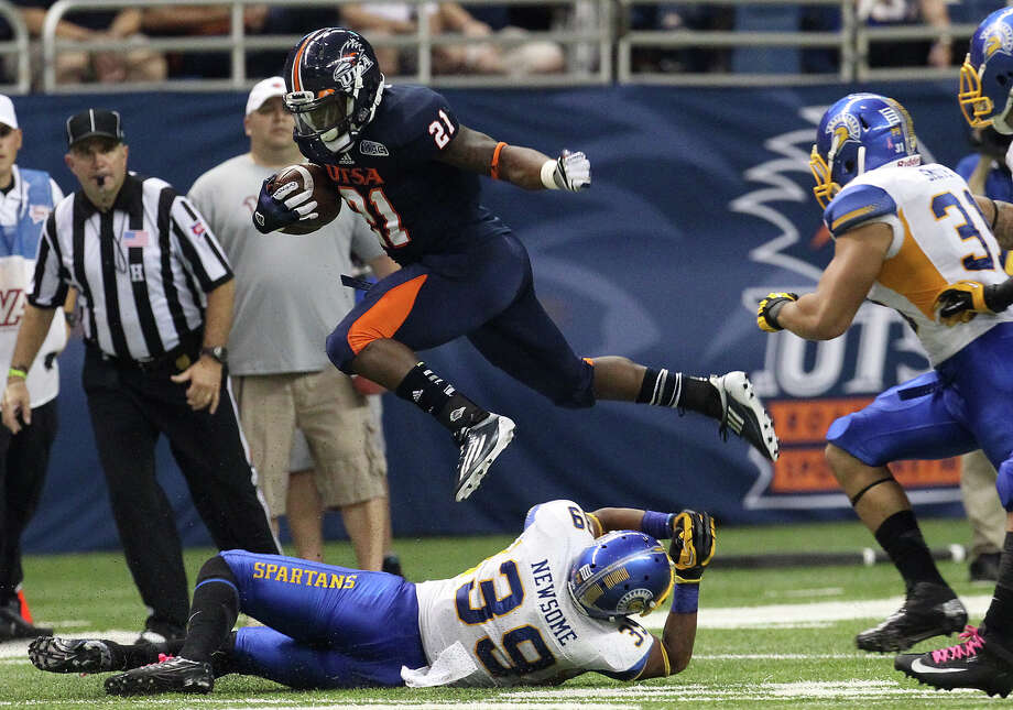 San Jose State 52 - UTSA 24: UTSA's Evans Okotcha (21) leaps over San Jose State's Cullen Newsome (39) in the first half at the Alamodome on Saturday, Oct. 20, 2012. Photo: Kin Man Hui, Express-News / © 2012 San Antonio Express-News