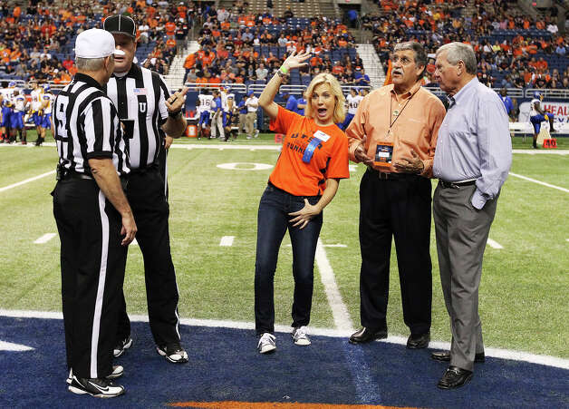 UTSA alumni and NBC Sports reporter Michelle Beadle (center) waves to fans while standing beside UTSA President Ricardo Romo and NuStar Energy chairman Bill Greehey prior to the coin toss in the game between UTSA and San Jose State at the Alamodome on Saturday, Oct. 20, 2012. Photo: Kin Man Hui, Express-News / © 2012 San Antonio Express-News