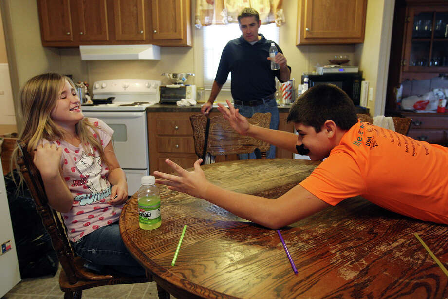 Mark Bradbury watches as daughter Jade, 10, and son Dylan, 14, play a game of paper football. Bradbury and his son live together, and his daughters were visiting. Photo: Jerry Lara, San Antonio Express-News / © 2012 San Antonio Express-News