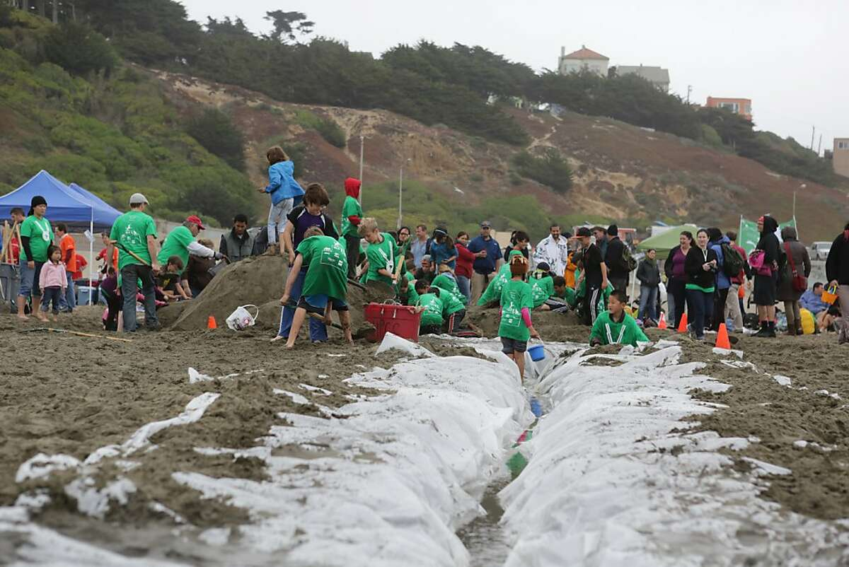 A plastic tarp reservoir filled with water leads to Miraloma Elementary School team members who are working on their sand castle.