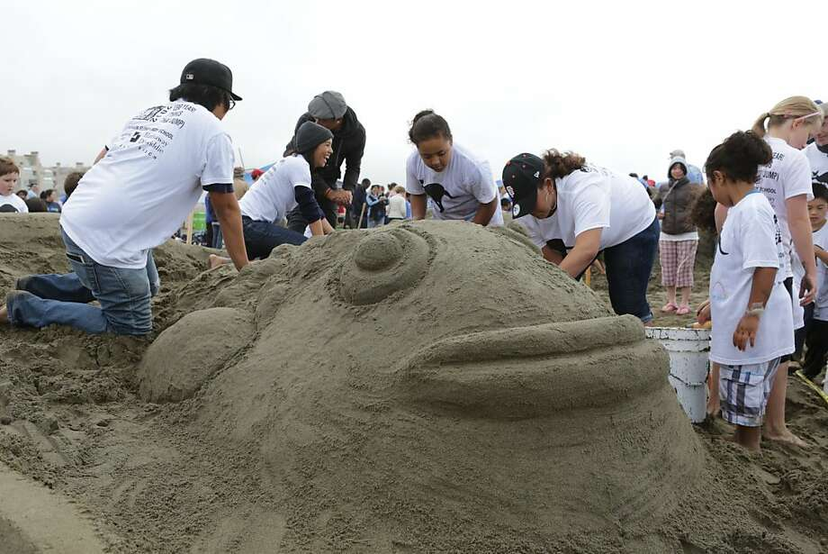 Team members from Jefferson Elementary School help to carve one of two fish jumping out of 3D glasses. Hundreds of people turned out for the annual LEAP Sand Castle Contest at Ocean Beach in San Francisco on Saturday. The charity event supports arts in education programs. Photo: Rashad Sisemore, The Chronicle