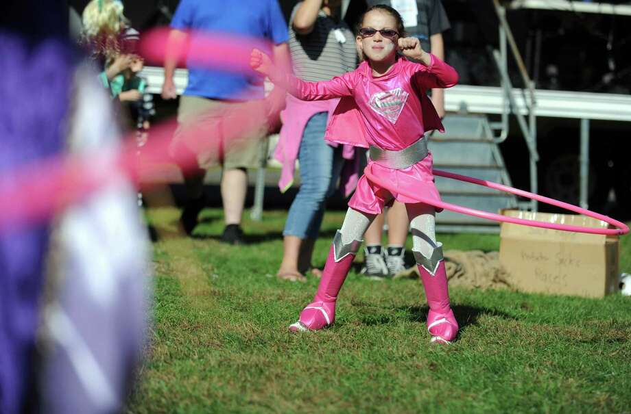Seven-year-old Super Girl, Abbey Adintori, of Stratford, competes in a hula hoop competition during the annual Great Pumpkin Festival Saturday, Oct. 20, 2012 at Boothe Memorial Park in Stratford, Conn. Photo: Autumn Driscoll / Connecticut Post