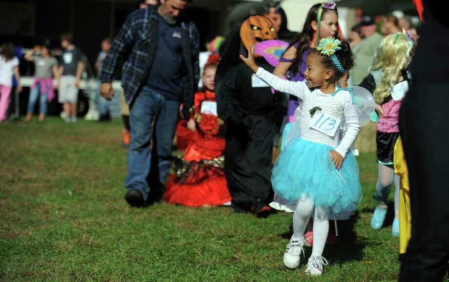 Five-year-old Hailey Connor, of Stratford, waves to her mom as she marches in the costume parade during the annual Great Pumpkin Festival Saturday, Oct. 20, 2012 at Boothe Memorial Park in Stratford, Conn. Photo: Autumn Driscoll / Connecticut Post
