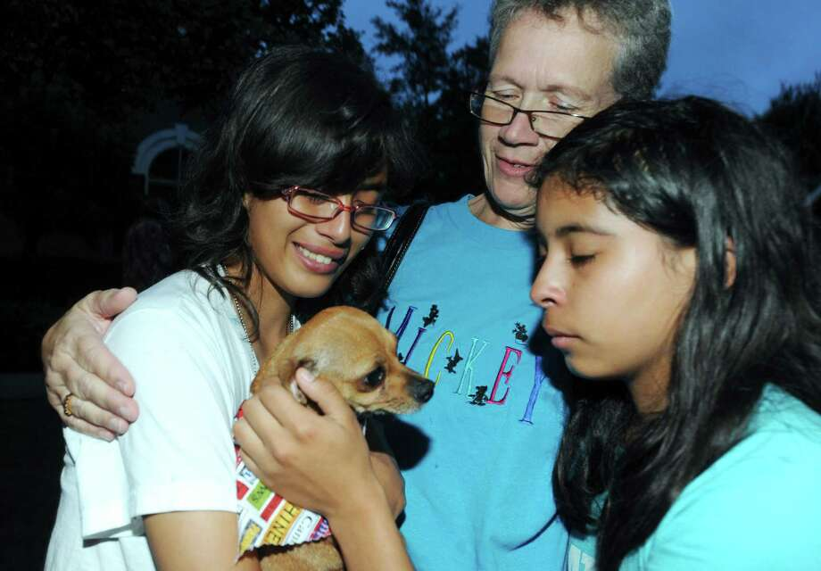 Emily (from left), Shelley and Frances Kendall bid farewell to Claire, the dog that they have fostered for three months, before returning her to the Alamo Rescue Friends group that will transport her to Nashua, N.H., for adoption on Sept. 29, 2012. Dogs were transported from San Antonio to the Humane Society for Greater Nashua. Photo: Billy Calzada, San Antonio Express-News / © San Antonio Express-News
