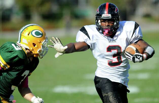 Fairfield Warde's Kerven Jaques stiff-arms Trinity Catholic's Shawn Crowell on his way to a touchdown during Saturday's football game at Trinity Catholic High School in Stamford, Conn., on October 20, 2012. Photo: Lindsay Niegelberg / Stamford Advocate