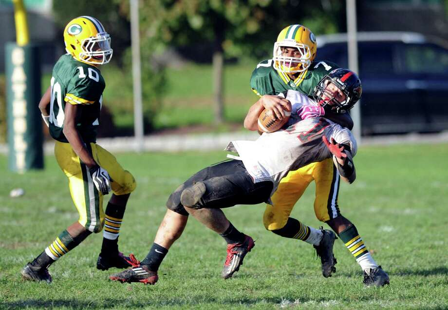 Fairfield Warde's Max Garrett is tackled by Trinity Catholic's Neno Merritt during Saturday's football game at Trinity Catholic High School in Stamford, Conn., on October 20, 2012. Photo: Lindsay Niegelberg / Stamford Advocate