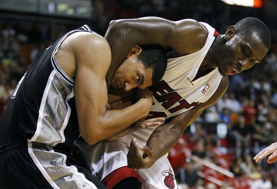 San Antonio Spurs' Danny Green, left, and Miami Heat's Terrel Harris wrestle for the ball during the second half of an NBA basketball game in Miami, Saturday, Oct. 20, 2012. The Heat won 104-101. (J Pat Carter/Associated Press)