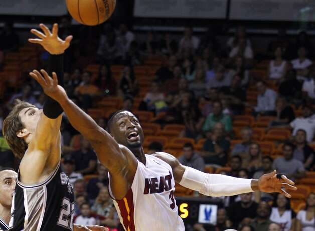 San Antonio Spurs' Tiago Splitter (22) tries to block Miami Heat's Dwyane Wade (3) during the first half of an NBA basketball game in Miami, Saturday, Oct. 20, 2012.  (J Pat Carter/Associated Press)
