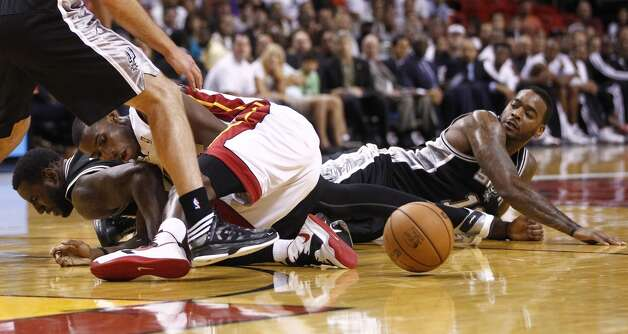 Miami Heat's Terrel Harris (white shorts) wrestles DeJuan Blair, left, and Josh Powell, right, for the ball during the second half of an NBA basketball game in Miami, Saturday, Oct. 20, 2012.  (J Pat Carter/Associated Press)