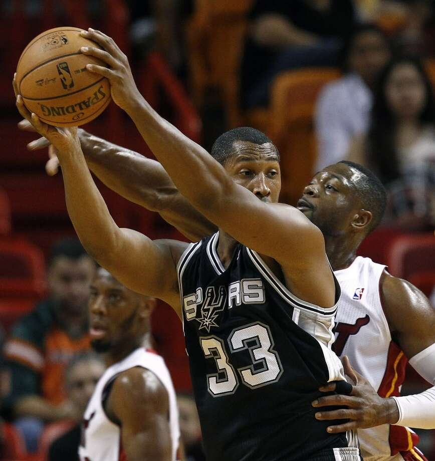 Miami Heat's Dwyane Wade, right, tries to steal the ball from San Antonio Spurs' Boris Diaw (33) during the first half of an NBA basketball game in Miami, Saturday, Oct. 20, 2012.  (J Pat Carter/Associated Press)
