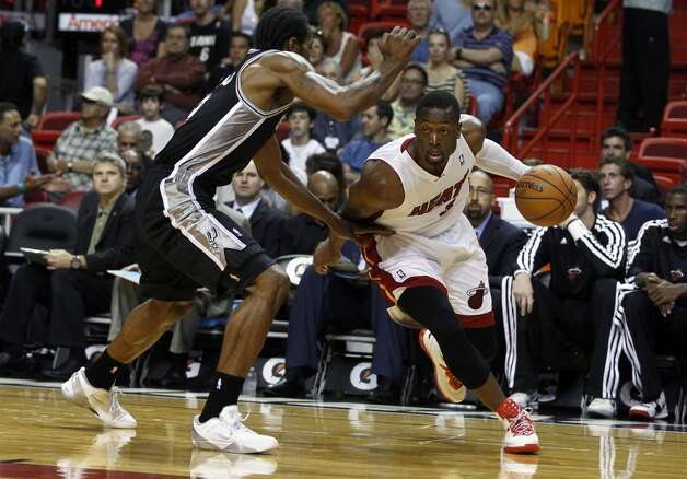 Miami Heat's Dwyane Wade (3) drives around San Antonio Spurs' Kawhi Leonard during the first half of an NBA basketball game in Miami, Saturday, Oct. 20, 2012. (J Pat Carter/Associated Press)