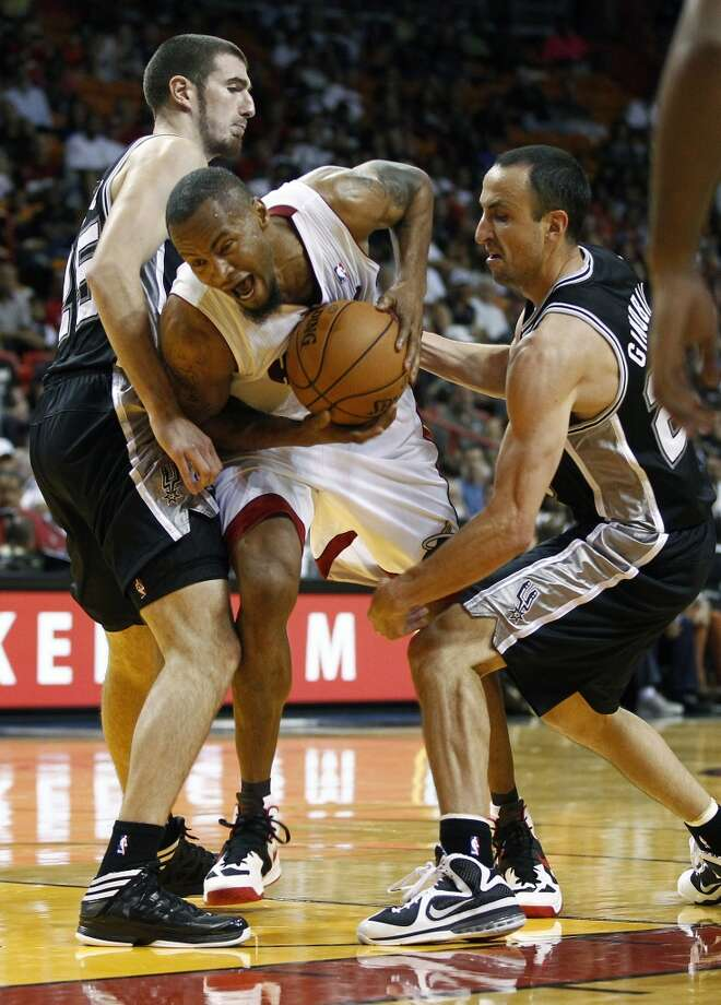 San Antonio Spurs players Nando De Colo (25) and Manu Ginobili, right, try to block Miami Heat's Rashard Lewis, center, during the second half of an NBA basketball game in Miami, Saturday, Oct. 20, 2012. (J Pat Carter/Associated Press)