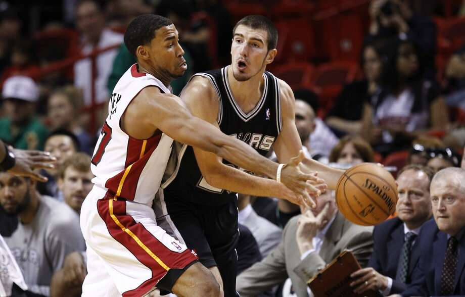 Miami Heat's Garrett Temple, left, tries to steal the ball from San Antonio Spurs Nando De Colo during the first half of an NBA basketball game in Miami, Saturday, Oct. 20, 2012. (J Pat Carter/Associated Press)