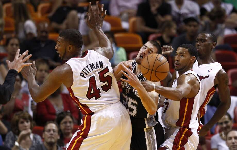 San Antonio Spurs' Nando De Colo (25) reacts after Miami Heat players Dexter Pittman (45) and Garrett Temple (17) force him to let go of the ball during the first half. (J Pat Carter/Associated Press)