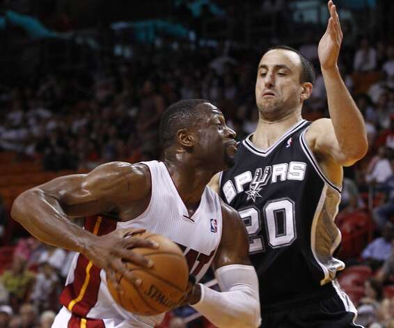 San Antonio Spurs' Manu Ginobili (20) tries to block Miami Heat's Dwyane Wade during the first half of an NBA basketball game in Miami, Saturday, Oct. 20, 2012. (J Pat Carter/Associated Press)