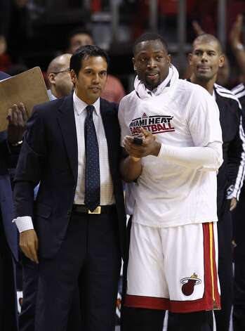Miami Heat coach Erik Spoelstra, left, and Dwyane Wade watch the final minute of NBA basketball game action against the San Antonio Spurs in Miami, Saturday, Oct. 20, 2012. The Heat won 104-101.  (J Pat Carter/Associated Press)