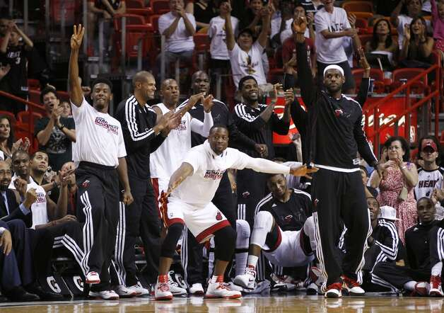 Miami Heat players Norris Cole, left, Dwyane Wade, center, and LeBron James, right, celebrate during the second half of an NBA basketball game against the San Antonio Spurs in Miami, Saturday, Oct. 20,  2012. (J Pat Carter/Associated Press)