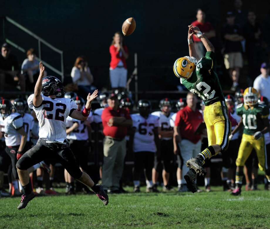 Trinity Catholic's Tom Costigan hits the tip of a Fairfield Warde pass which was  intended for Dan Skelton but fell incomplete during Saturday's football game at Trinity Catholic High School in Stamford, Conn., on October 20, 2012. Photo: Lindsay Niegelberg / Stamford Advocate