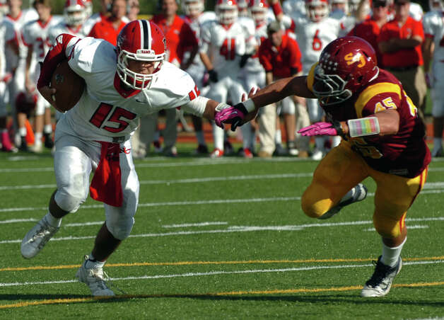In this play New Canaan QB Nick Cascione carries the ball toward the endzone to score a touchdown, during boys football action against St. Joseph in Trumbull, Conn. on Saturday October 20, 2012. At right is St. Joe's #45 Mike Pulaski. Photo: Christian Abraham / Connecticut Post