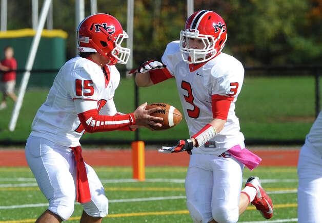 New Canaan QB Nick Cascione hands off the ball to #3 Jack Gilio, during boys football action against St. Joseph in Trumbull, Conn. on Saturday October 20, 2012. Photo: Christian Abraham / Connecticut Post